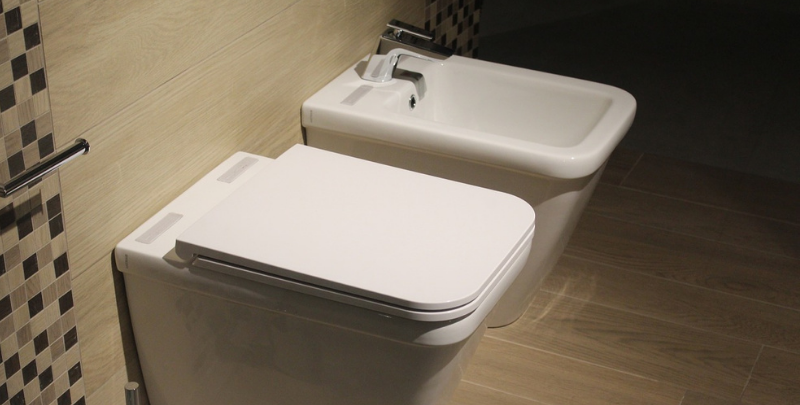 toilet with concealed cistern next to bidet