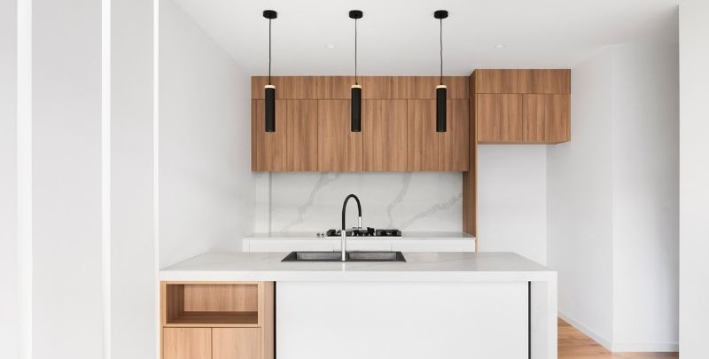 white kitchen with timber cabinets and black tapware