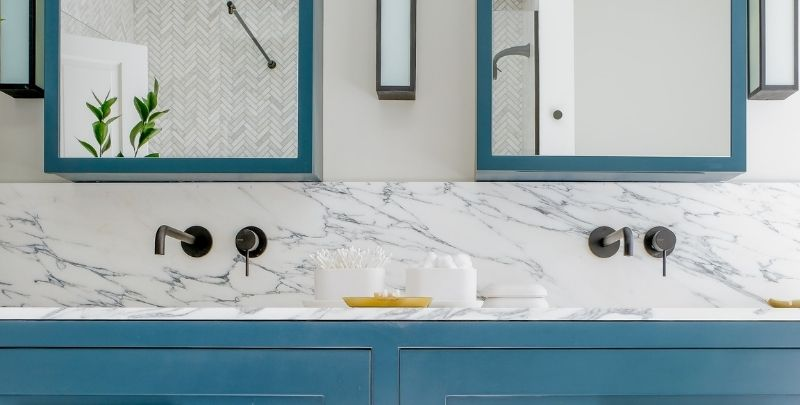 white marble bathroom with blue cabinets and black tapware