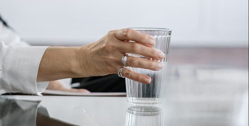 woman holding glass of water at table