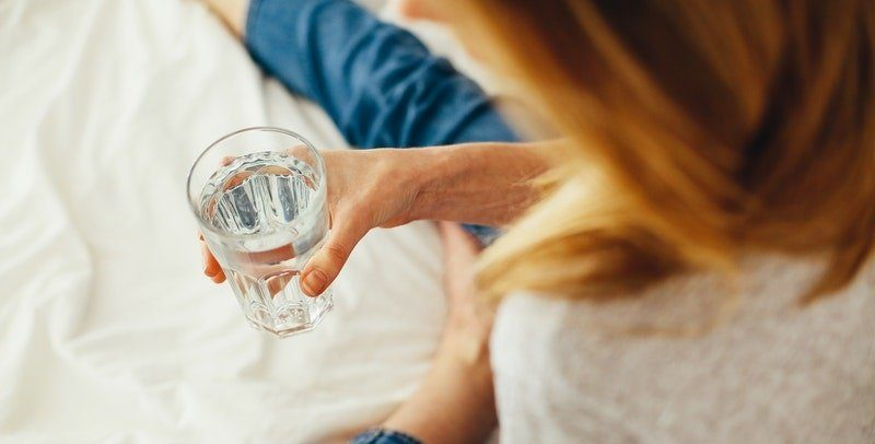 woman sitting on white sheets drinking glass of water