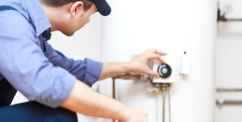 plumber adjusting hot water system thermostat