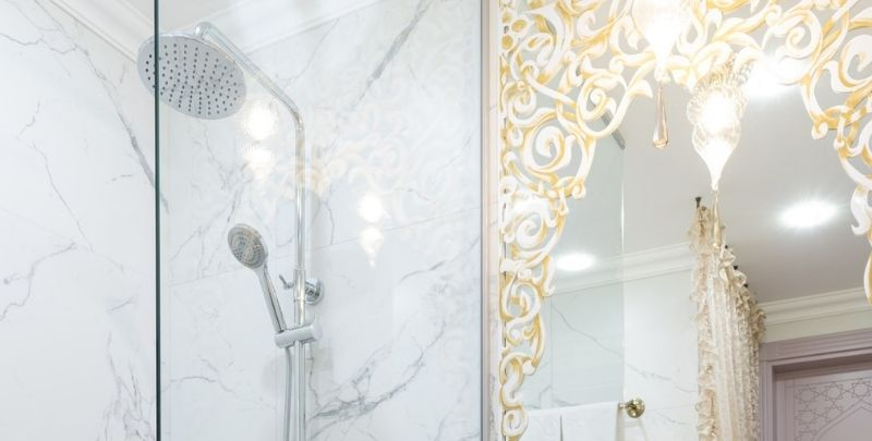 dual shower head in white and gold bathroom