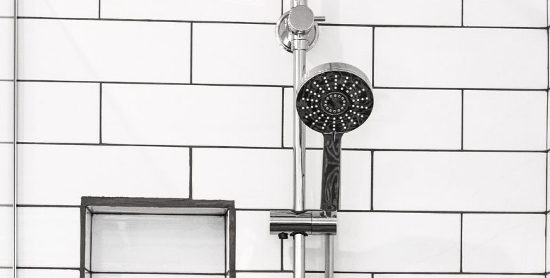 rail shower head in white bathroom