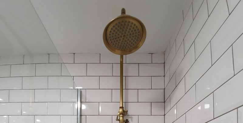 rain shower head in white bathroom