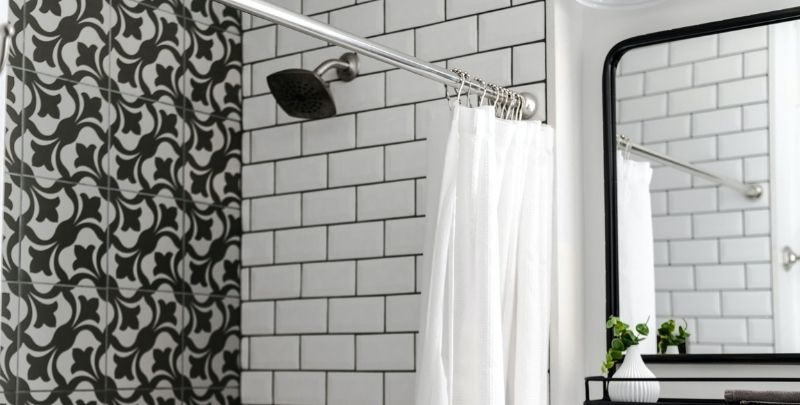 wall mounted shower head in black and white bathroom